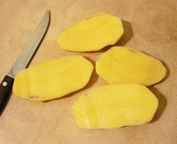 Чистим картошку и разрезаем ее пополам