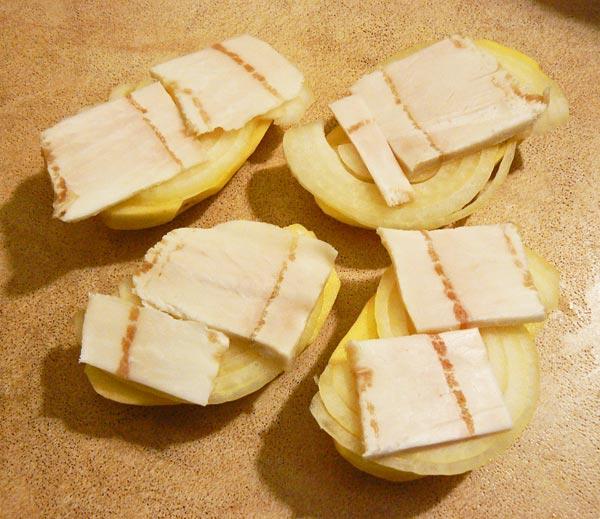 Сверху картошки с луком укладываем кусочки сала