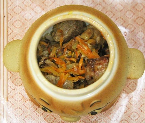 Наполняем керамические горшочки для запекания рисом и жареной свининой с луком и морковкой