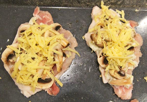 На свиные отбивные выкладываем нарезанные шампиньоны, лук, сверху тертый твердый сыр