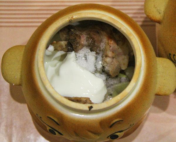 Куски кролика помещаем в глиняный горшочек для запекания, добавляем лук, специи, сметану