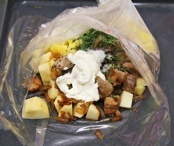 В пакет для запекания помещаем картошку, зажарку, соль, специи, сметану